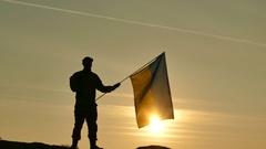 4K. Soldier silhouette salute Ukrainian Flag, sunrise time   Stock Footage