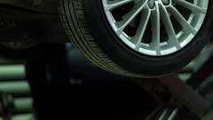 Car raised on a lift in a service station Stock Footage