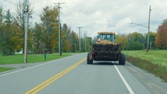 Tractor rides on the road slowly, prevents drive car. New York State, USA A Stock Footage