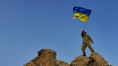 4K. Soldier silhouette waves Ukrainian Flag, against blue sky   Stock Footage