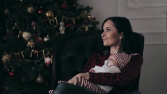 Young mother with a newborn baby and daughter near Christmas tree Stock Footage