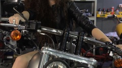 Female biker leans on the motorcycle tank Stock Footage