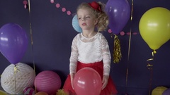 Portrait of little cute girl throwing red balloon on her birthday party Stock Footage