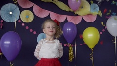 Cute baby girl catching bright confetti and celebrating her birthday party Stock Footage