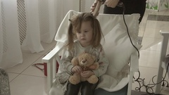 Hairstylist making curls using a hair iron to little pretty girl be beautiful Stock Footage