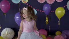 Pretty little baby girl laughing and blowing a kiss on her birthday party Stock Footage