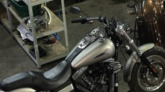 Female biker poses on the chopper at the motorcycle workshop Stock Footage