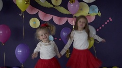 Two pretty baby girls sisters dancing and celebrating on birthday party Stock Footage