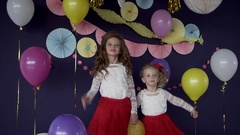 Two baby girls sisters waving and celebrating on birthday party Stock Footage