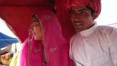 Handheld shot of Indian couple enjoying a camel ride in a caravan at Pushkar Fai Stock Footage
