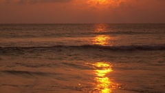 Seascape view of tropical beach in gold colors with flecks of sunlight on water Stock Footage