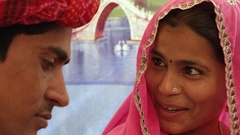 Closeup of Indian couple having a discussion sitting with a colourful background Stock Footage