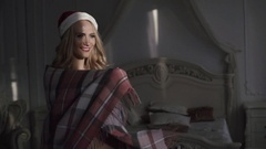 Young sexy girl in santas hat is wrapping up in a warm blanket Stock Footage