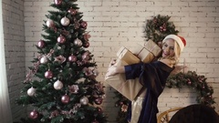 Young sexy girl in beautiful lingerie is happy to hold a lot of gifts near the Stock Footage