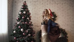 Young beautiful girl in sexy lingerie is whirling near the Christmas Tree Stock Footage