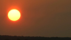 In a summer haze the sun at sunset changes the color on yellow and red. Stock Footage