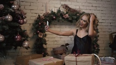 Young sexy girl is making selfies among Christmas gifts near the New Year Tree Stock Footage
