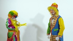 Short funny clown scares the other clown with huge scissors Stock Footage