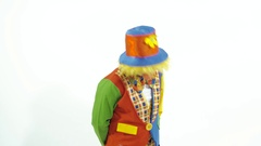 Portrait of shy clown in colorful hat giving a box as a present Stock Footage