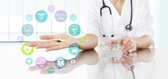 Doctor with pills in hand and colored icons. Health care and medical concept Kuvituskuvat