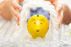 Protect your savings concept with bubble wrap covering a yellow piggy bank Stock Photos