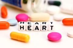 Medical drugs and letter cubes spelling heart, suggesting cardiac problems Stock Photos