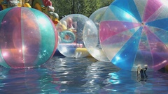 Big inflatable balls floating on the water in pool Stock Footage