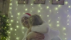 Hugging mother and daughter near the Christmas tree Stock Footage