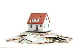 Model house on top of money pile suggesting savings for a house Stock Photos