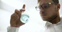 Scientist in laboratory examining liquid in glass beaker Stock Footage