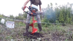 The man in the village bore holes Moto borer. Stock Footage