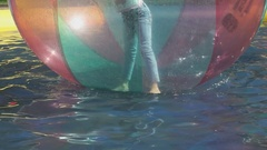 Little girl flounders inside large inflatable ball Stock Footage