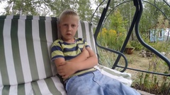 Little blond boy  says, swinging on the swing in the summer nature Stock Footage