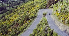 Aerial of car driving on a remote country road south island of New Zealand Stock Footage