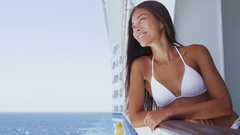 Young woman in swimsuit standing on cruise ship at sunny day looking at sea Stock Footage