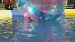 Little boy flounders inside a big inflatable ball Stock Footage
