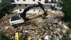 Excavator bulldozer works to get rid of the rubbish at demolition site Stock Footage