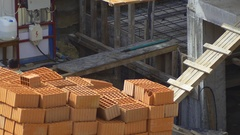 Worker loads bricks manually on to the crane pallet during construction building Stock Footage