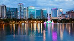 Orlando, Florida City Skyline on Lake Eola as Night Falls (logos blurred) Stock Photos