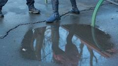 Girl wearing black combat boots splashing in a puddle after rain Stock Footage