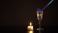 Burning sambuka with a gas lighter near a small candle Stock Footage