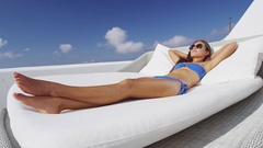Asian woman relaxing lounging on white outdoor beach sofa daybed Stock Footage