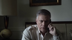 Man in his living room talking on the cell phone 4k Stock Footage