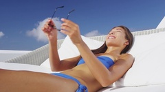Woman putting on sunglasses sun tanning on luxury vacation Stock Footage