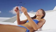 Woman putting on sunglasses sun tanning on luxury vacation Stock Footage