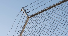 Looking up at a barbed wire fence - POV - 4k Stock Footage