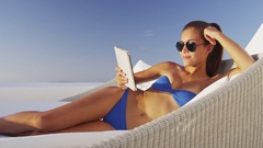 Woman reading book on e-book e-reader tablet relaxing in sofa chair Stock Footage