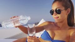 Girl pouring water from water bottle drinking relaxing wearing bikini Stock Footage