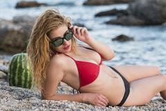 Woman with amazing body in tanga bikini by the rocky sea, rocks ocean and w.. Stock Photos