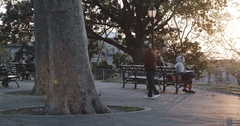 Unrecognizable person sitting on a park bench at sunset - 4k Stock Footage